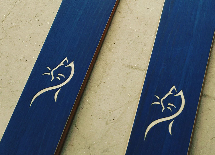customization on a blue wood finish pair of skis , with the laser engraving of a cat drawing